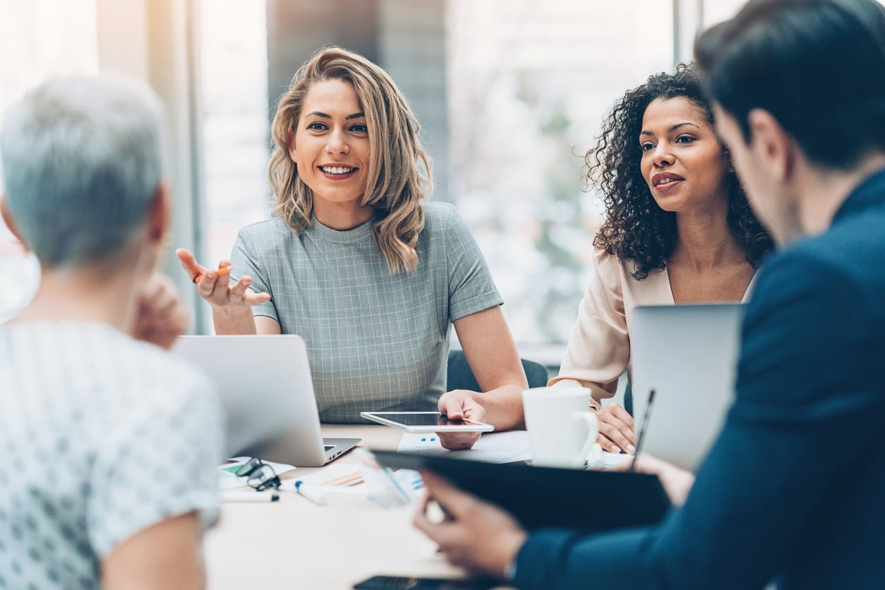 Smiling business women talk to colleagues