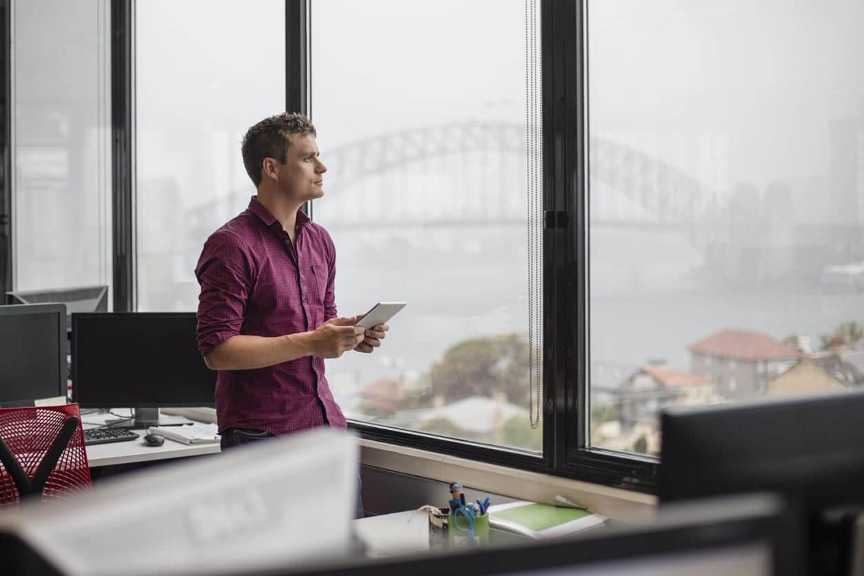 Businessman using tablet computer in office, he's looking through the window with the Sydney harbour bridge in the background.