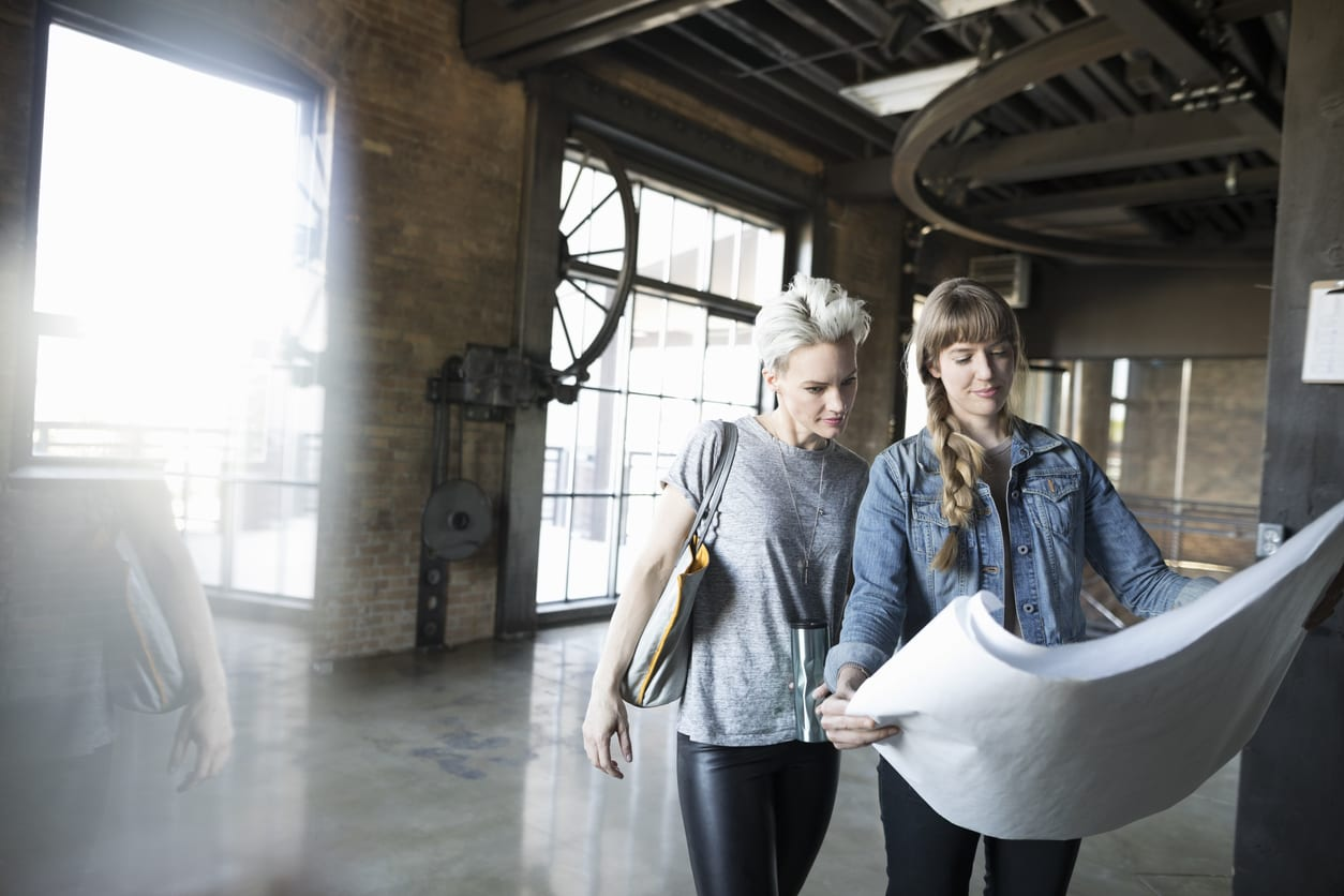 Female architects reviewing blueprints in new industrial open plan office