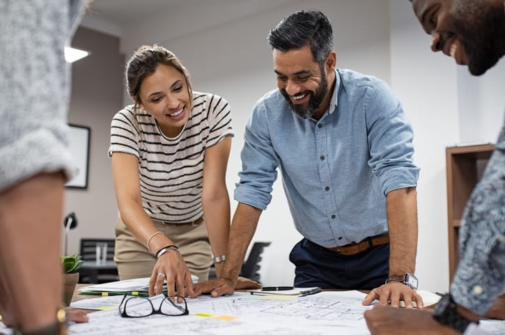 Team of multiethnic architects working on construction plans in meeting room. Cheerful engineers discussing on project in office. Group of mature businessman and young woman standing around table working on blueprint.