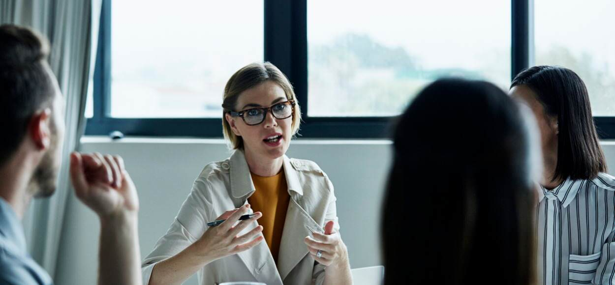business woman discussing with three colleagues in office