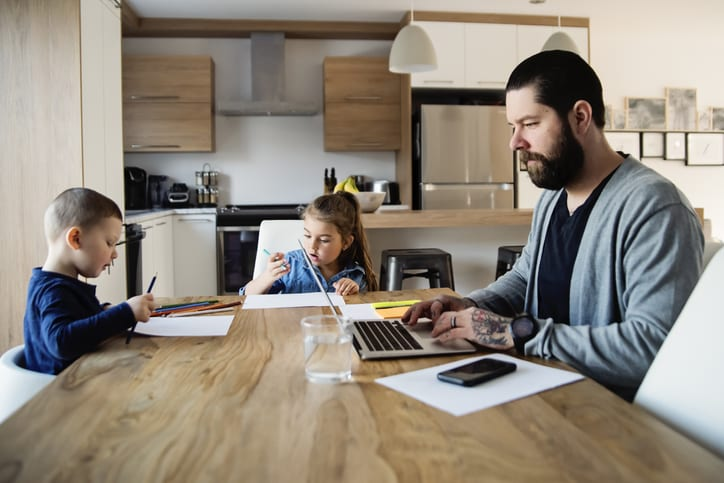 man working from home with kids at kitchen table