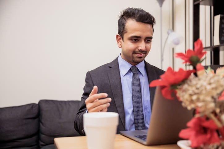 Work from home, Technology, Communication - Young man wearing suit and tie presenting his views over a video conference call.