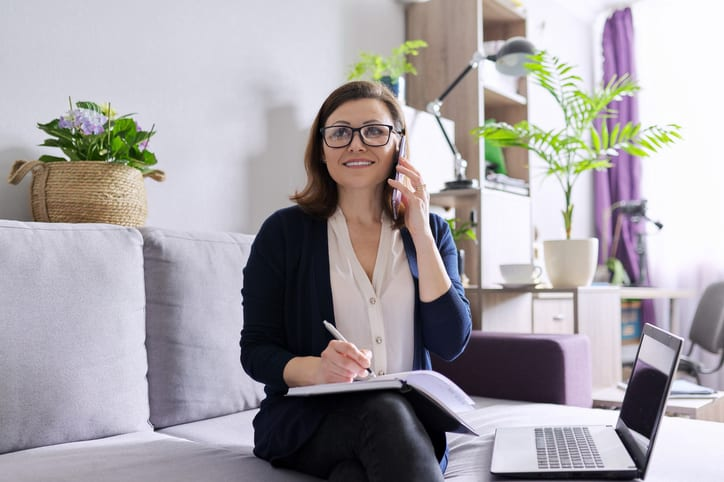 Mature woman working remotely at home, business female freelancer sitting on sofa with laptop, talking on phone, taking notes in business notebook.