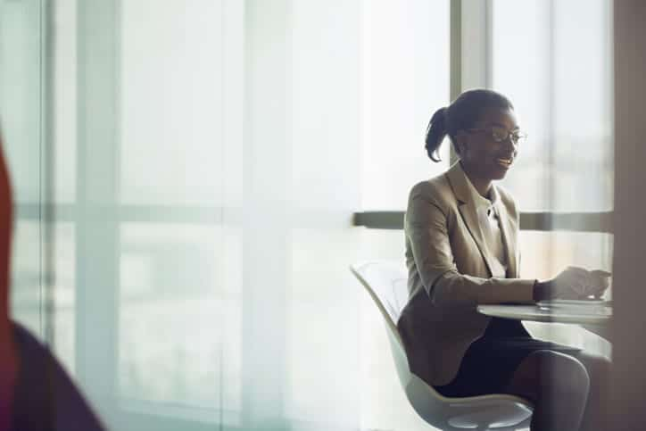 Young Black businesswoman sitting in meeting room area with anonymous client to explain discuss talk about products and services and ideas in bright sunny modern contemporary office space
