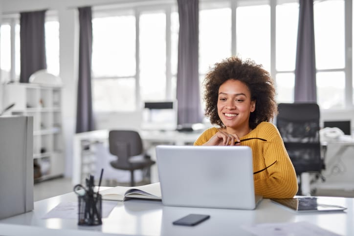 businesswoman smiling at her laptop
