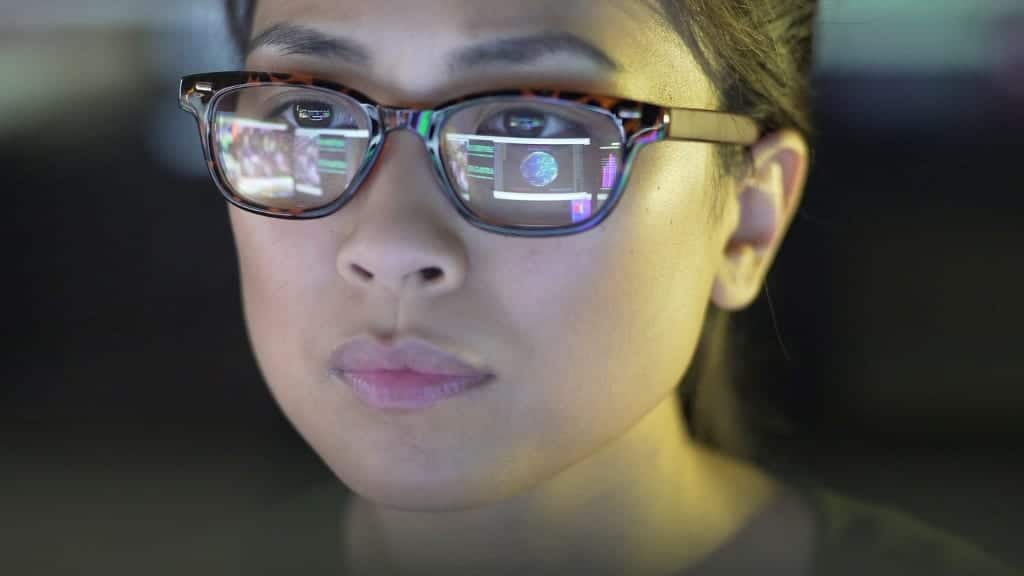 Woman looks at data on screen as it reflects through her glasses